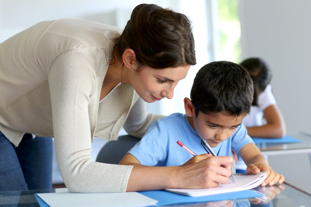 Teacher helping young boy with writing lesson-2